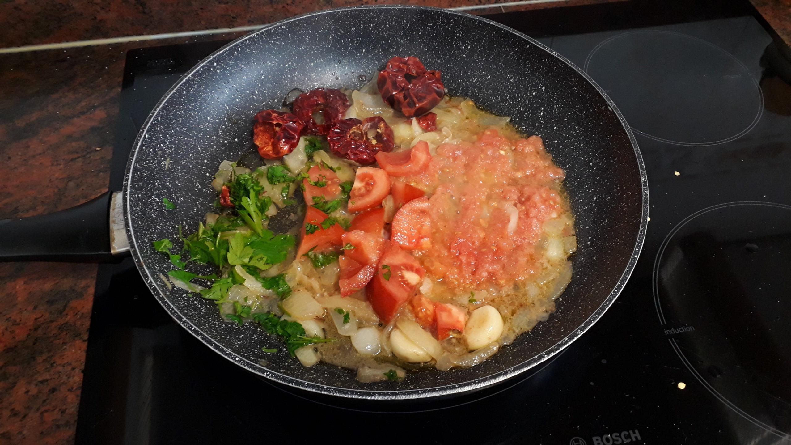 Sofriendo el tomate, la cebolla, el perejil y las ñoras