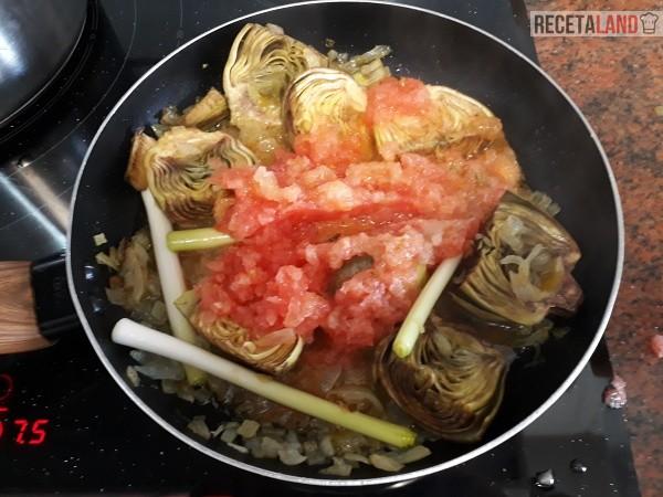 Sofriendo las alcachofas, los ajos tiernos y el tomate