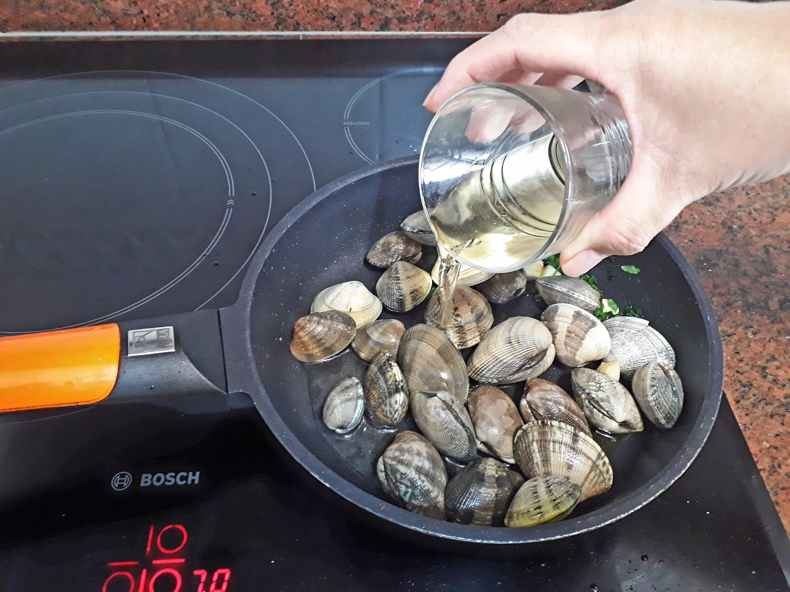 Añadiéndole el vino blanco a las almejas