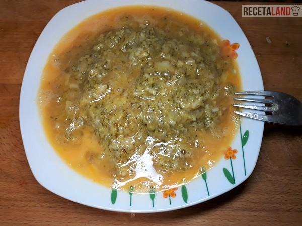 Plato con el frito en los huevos batidos para la tortilla