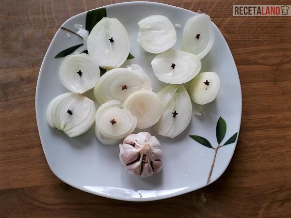 Cebolla cortada a rebanadas con clavo y cabeza de ajos
