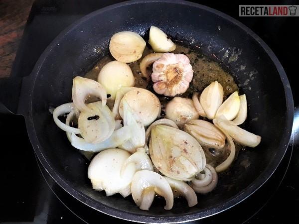 Rehogando la cebolla, los clavos y la cabeza de ajos