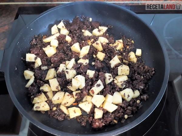 Añadiendo la manzana al frito de morcilla