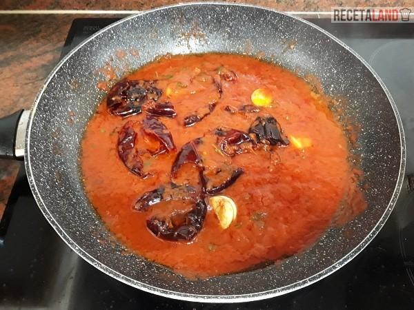 Mezclando en el sofrito del tomate los ajos y las ñoras