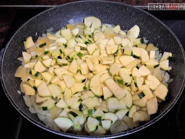 Añadiéndole el calabacín a las patatas con la cebolla